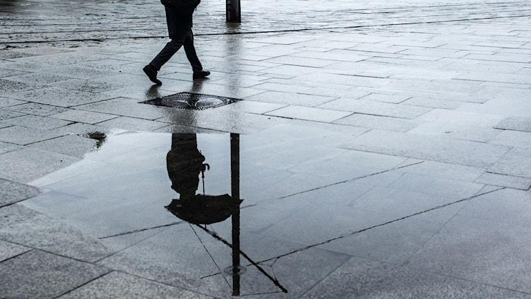 person med paraply speglas i regnpöl
