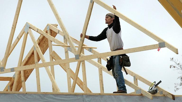 En man sätter upp takstolar på ett hus. Foto: Charles Krupa/Scanpix