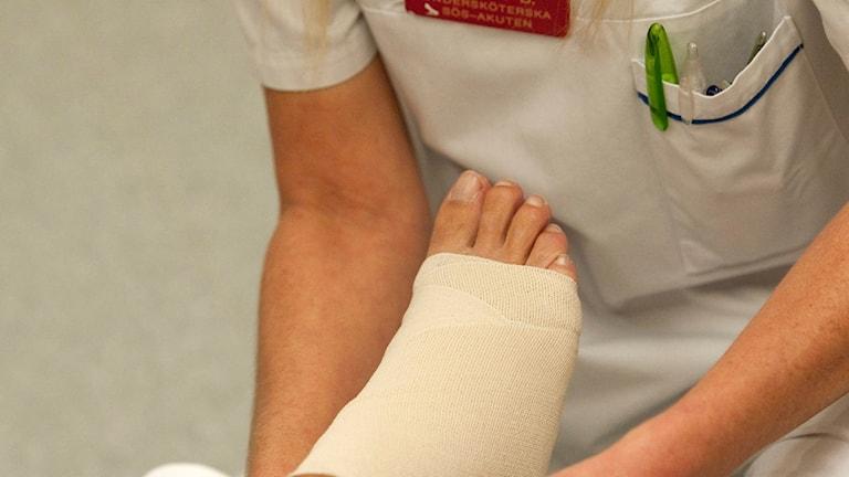 Undersköterska som lindar en fot.