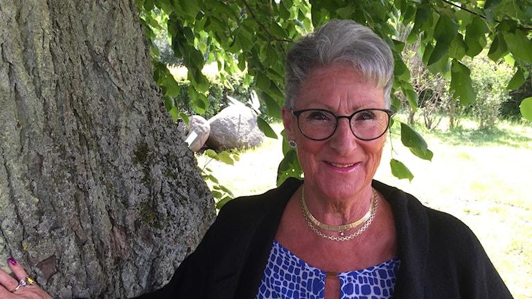 Korthårig äldre kvinna med glasögon. Hon står mot ett träd.