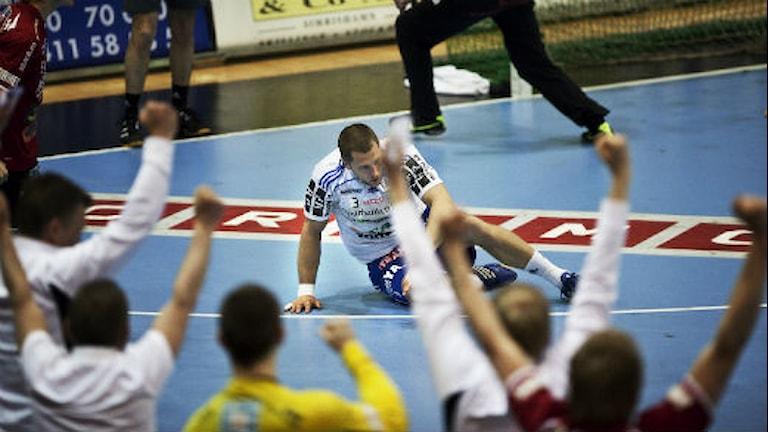 Ystadsspelare sitter på golvet, spelare i Drott jublar. Foto: Andreas Hillergren/Scanpix