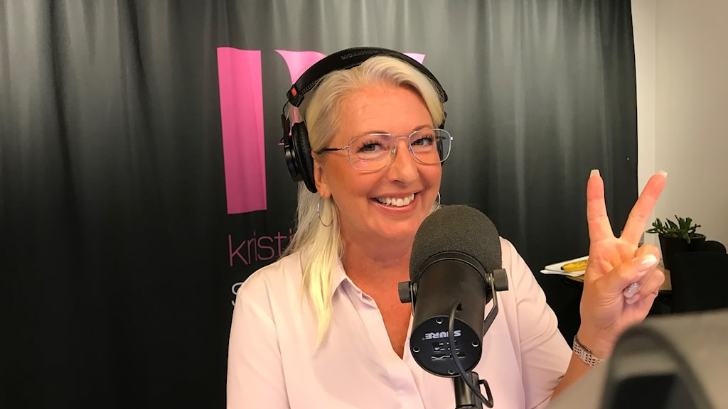 Blond kvinna i studio med hörlurar.