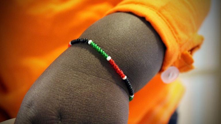 Lukas bär ett armband i Kenyas landsfärger. Foto: Johanna Darnéus/Sveriges Radio