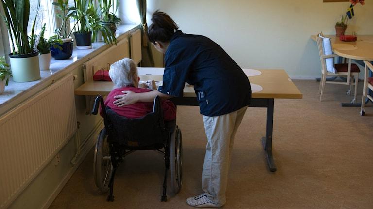 Person i rullstol får hjälp av undersköterska.