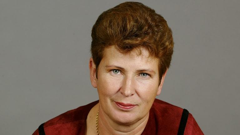 Porträtt på kvinna framför grå bakgrund.