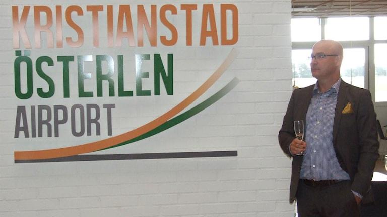 Flygplatsens VD Jonas Haak täcker av skylten med det nya namnet och logotyopen.