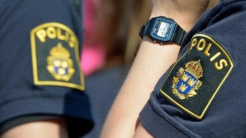 Överarmarna på två poliser som visar polisens emblem på tröjan. Foto: Bertil Enevåg Ericson/Scanpix
