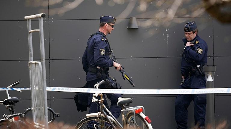 Poliser som går bakom en avspärrning