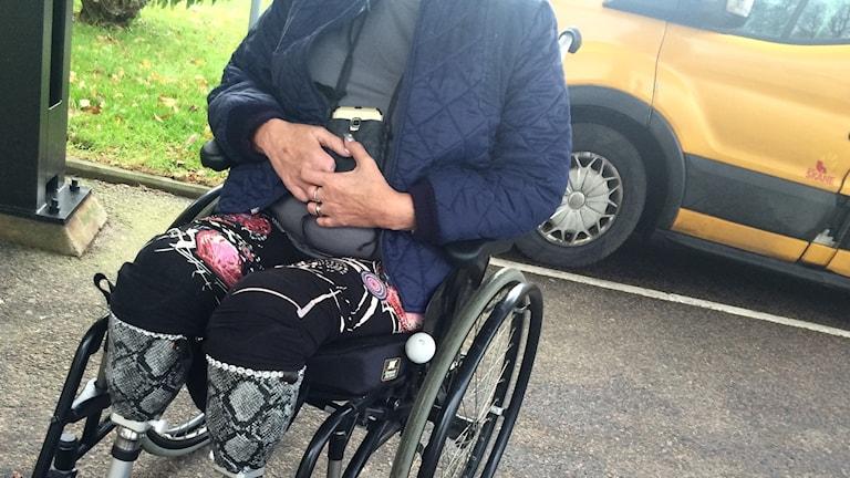 En anonym kvinna sitter i en rullstol intill en färdtjänstbil.