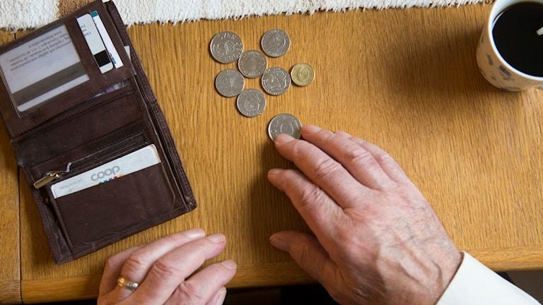 En pensionär räknar pengar vid köksbordet Foto: Fredrik Sandberg/ TT