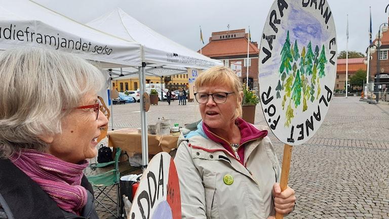 Två kvinnor med plakat.