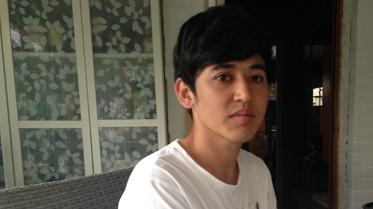 En ung man tittar in i kameran, sitter vid ett bord