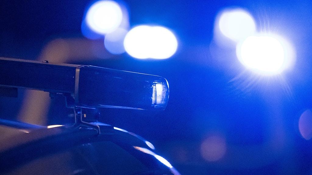 Polisbilar med blåsljus på mörk väg.
