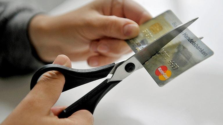 En person klipper sönder ett kontokort. Foto: Jessica Gow/TT