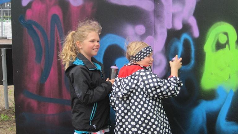 Ebba Rantzow och Elin Sjödin från Villanskolan i full färd med att inviga graffitiväggen. Foto: Bosse Johansson/Sveriges Radio
