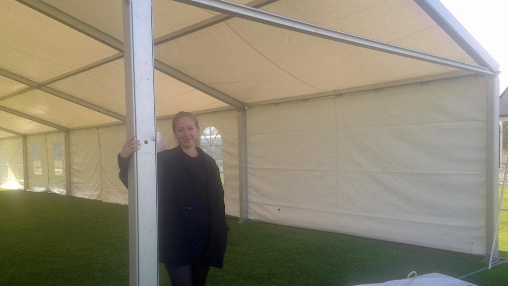 Arbetsförmedlaren Julia Lindbäck håller i en av pelarna till partytälten på Ivöstrands aktivitetspark där Bromöllas första jobbmässa ska hållas imorgon. Foto: Sarah Rätzer/Sverige Radio