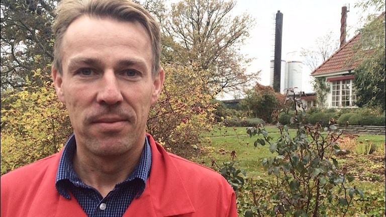 Bakom produktionschefen Christian Rosengren syns de två pelletstornen. Foto: Malin Rimfors/Sveriges Radio
