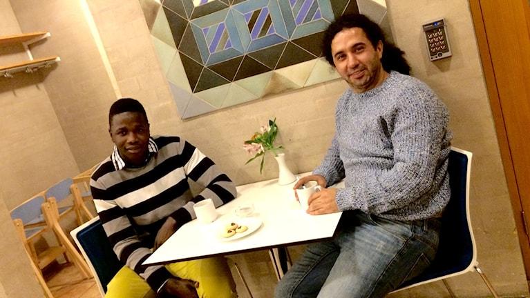 Två killar sitter vid ett litet bord och tittar in i kameran.