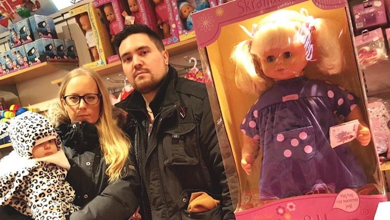 En familj står i en leksaksaffär bredvid en docka.