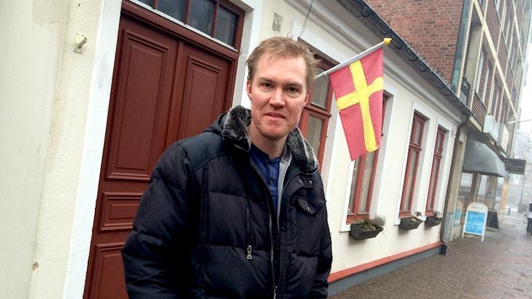 En man står framför en byggnad och ser in i kameran.