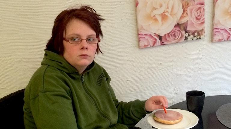 En tjej sitter vid ett bord och tittar in i kameran.