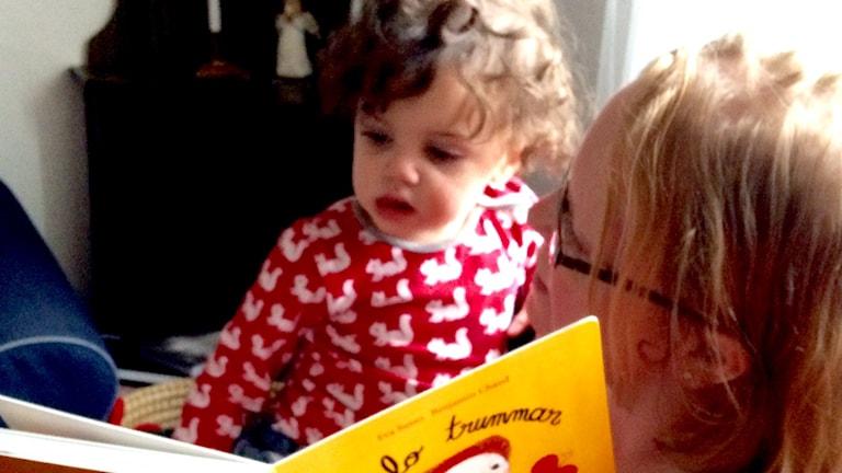 En kvinna sitter med sitt barn i knät och läser ur en bok.