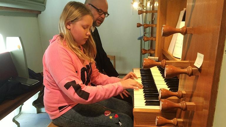 Bengt Almfjord lär Emma Ernstsson att spela orgel.