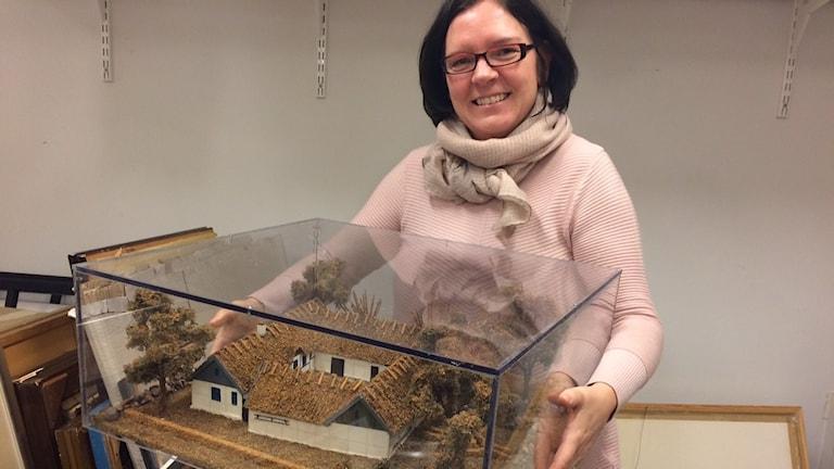 Kristin Svensson plockar fram ett minne från 20-talets Tomelilla. Då Sten Malmqvist bodde där. Foto: Malin Rimfors/Sveriges Radio