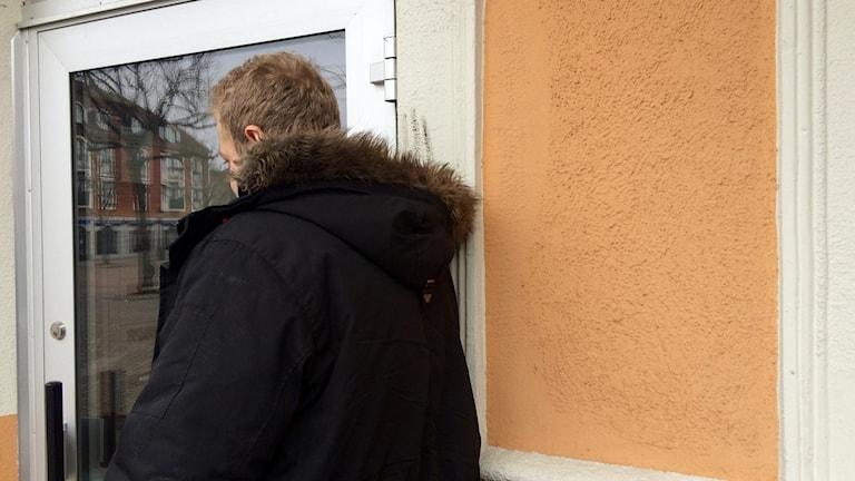En man står mot en vägg med ryggen mot kameran.