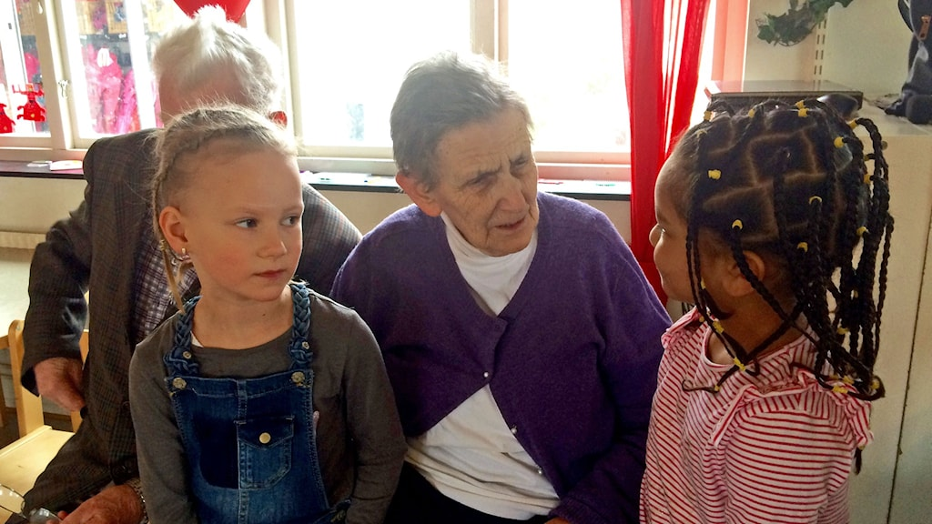 En äldre kvinna med två yngre barn bredvid sig.