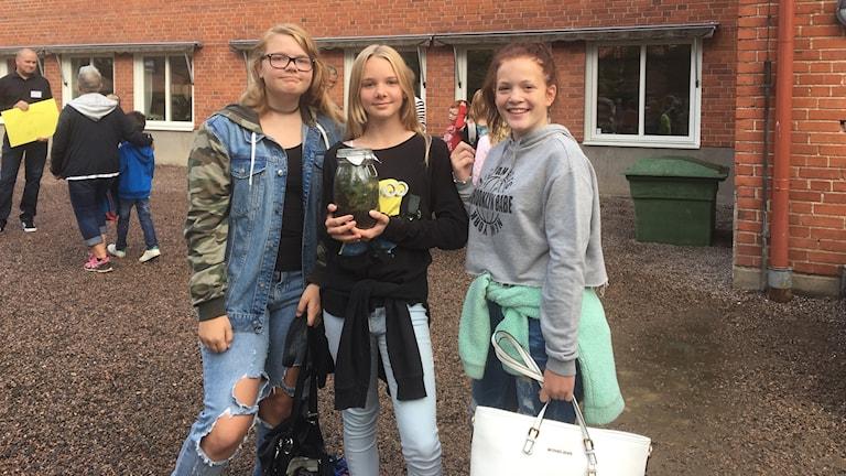 Tre tjejer tittar in i kameran, står framför tegelbyggnad.