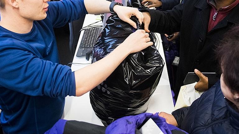 Butiksbiträde räcker över en plastpåse åt en kund över kassan