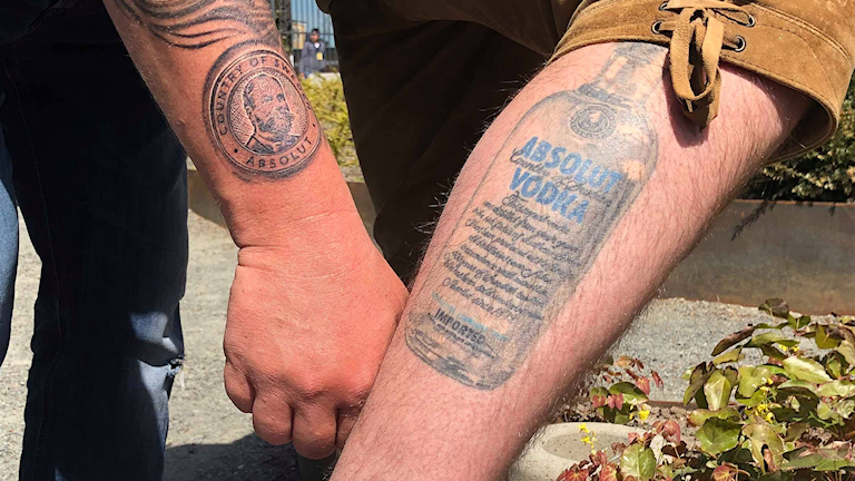Arm och ben tatuerade med Absolut vodka