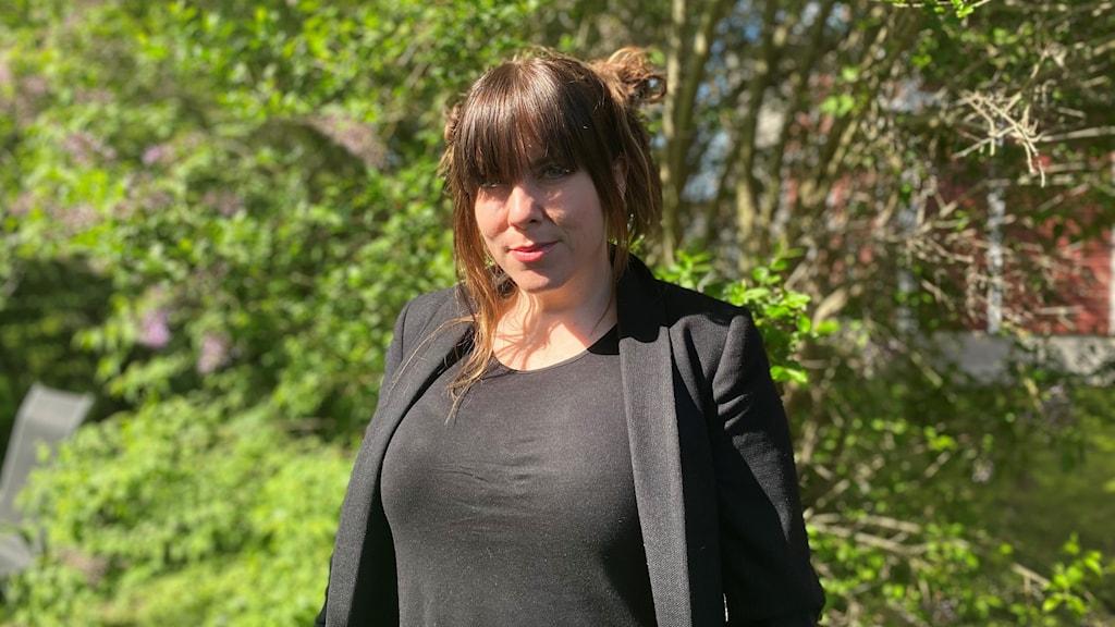 Kvinna som står utomhus, klädd i svart, framför en buske.