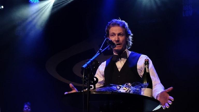 Man i vit skjorta och flyga bakom en mikrofon.