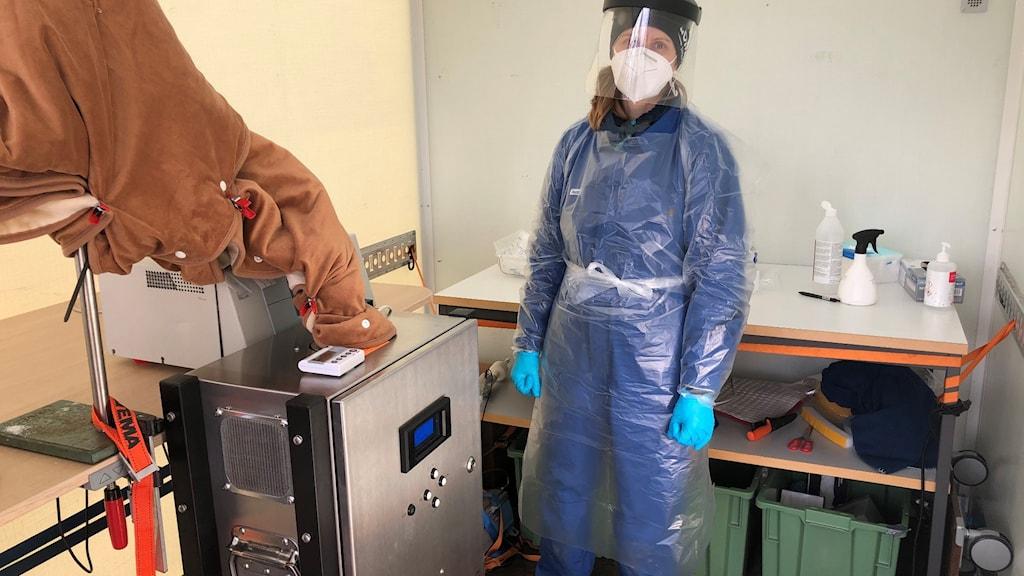 Malin Alsved står i skyddsutrustning inne i det mobila labbet.