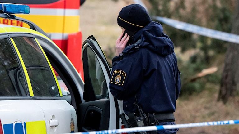 Polisman står bakom avspärrningar vid sin bil och pratar i telefon.
