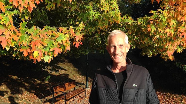 Äldre man i svart täckjacka i färgrikt höstlandskap