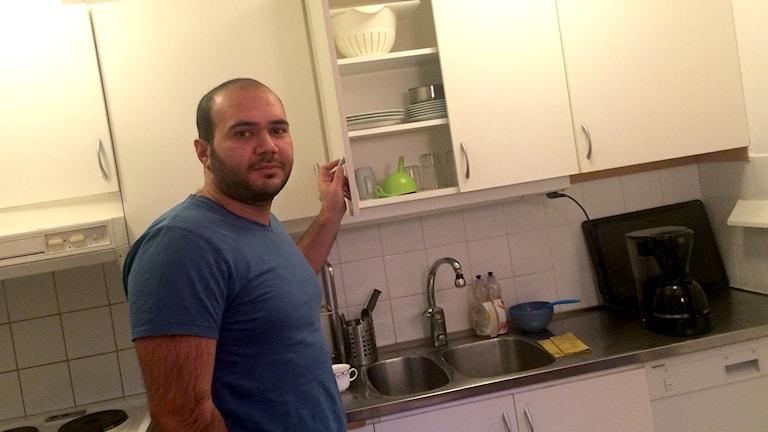 En man står i ett kök där han just öppnat en kökslucka.