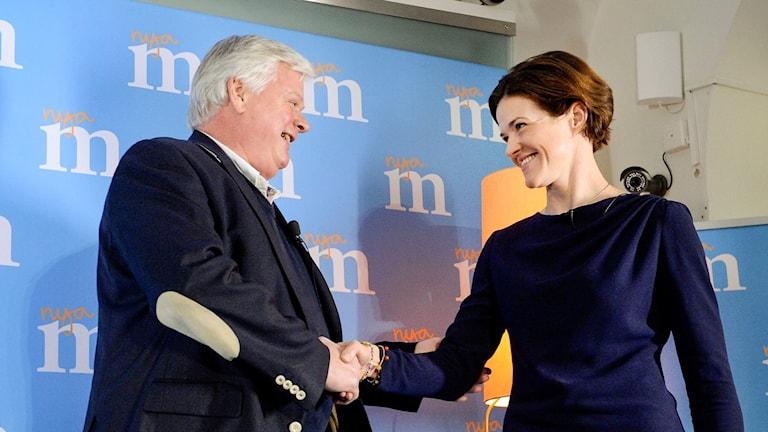 En gråhårig man tar en korthårig mörk kvinna i hand. I bakgrunden Moderaternas logotyp.