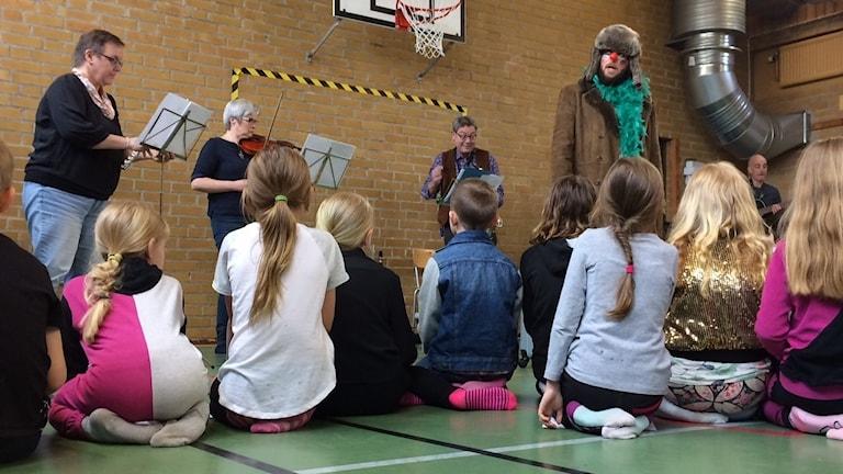 Clownen Rune lotsar barnen genom klarinett, trombon och fiol på Smedstorp skola.