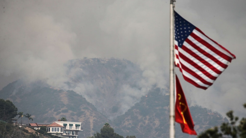 USA flagg. I bakgrunden kraftig rök från skogsbränder.