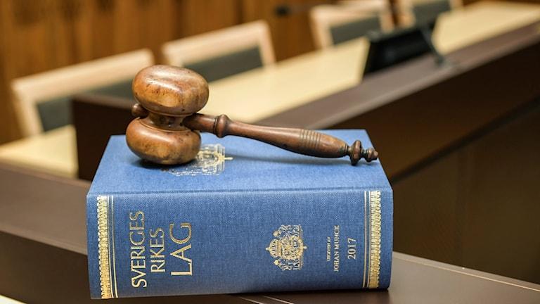Lagbok och domarklubba fotograferad inne i rättssal. Foto: Anders Wiklund/TT.