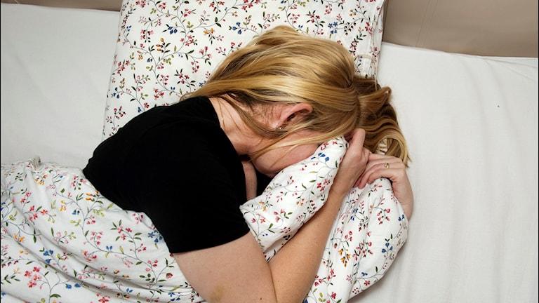 Kvinna i säng med täcket mot ansiktet