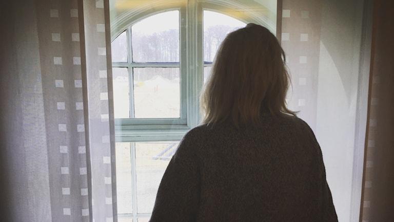 Kvinna kollar ut genom fönstret