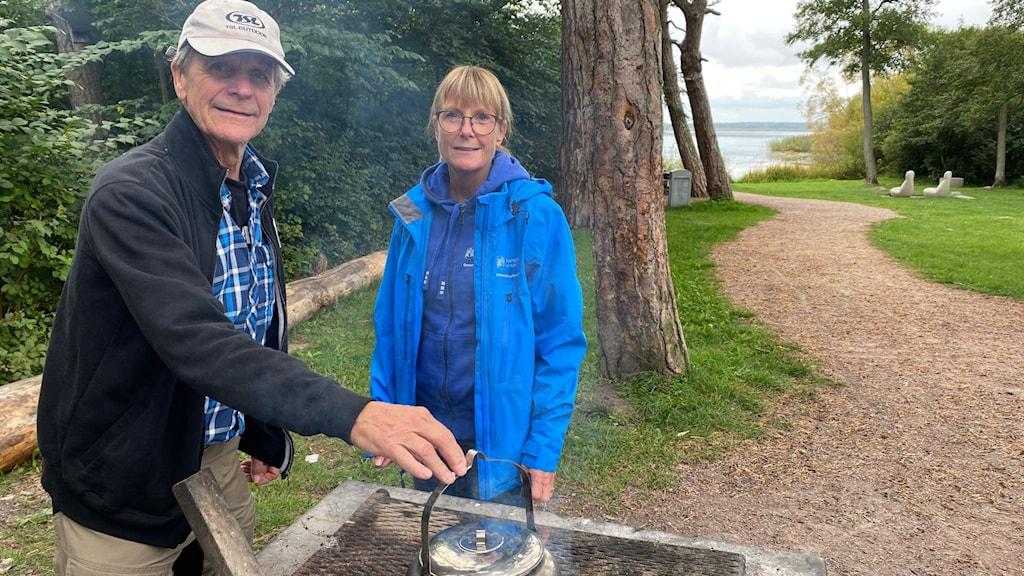 man och kvinna vid sjö kokar kaffe över öppen eld