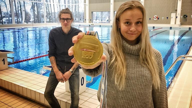 Blond flicka med guldmedalj och en kille med glasögon i bakgrunden. De befinner sig i en simhall.