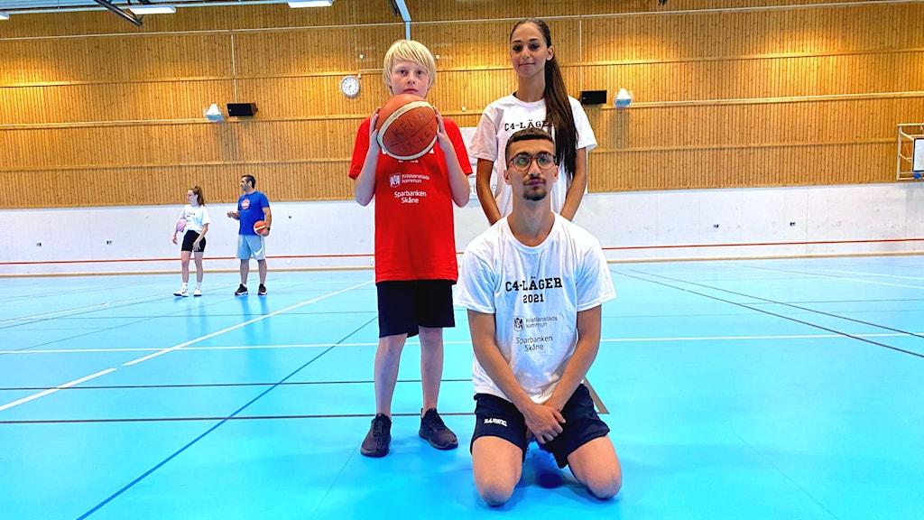 En pojke med röd tröja som håller i en basketboll, en tjej med mörkt hår och en kille som sitter på knä framför de båda. De är i en baskethall.