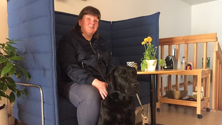 Kvinna med mörkt hår sitter i en blå soffa och klappar en svart ledarhund som sitter på golvet.