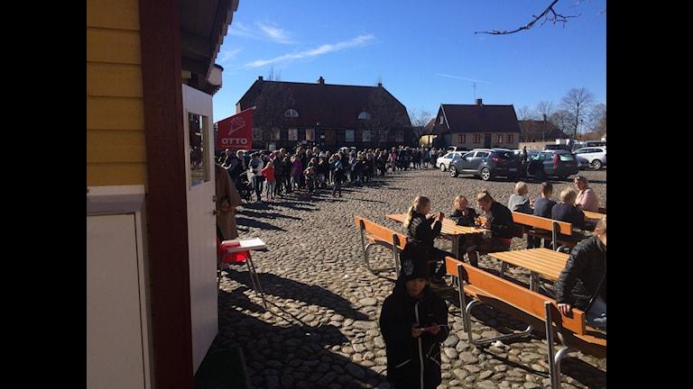 Torg med kullersten och en lång kö med människor i solsken.